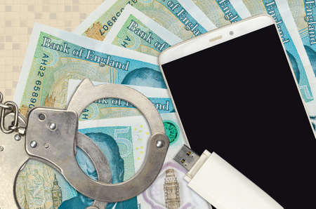 5 British pounds bills and smartphone with police handcuffs. Concept of hackers phishing attacks, illegal scam or online spyware soft distribution