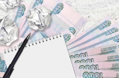 1000 russian rubles bills and balls of crumpled paper with notepad. Bad ideas or less of inspiration concept. Searching ideas for investment