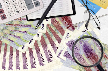 100 Cambodian riels bills and calculator with glasses and pen. Tax payment season concept or investment solutions. Searching a job with high salary earnings