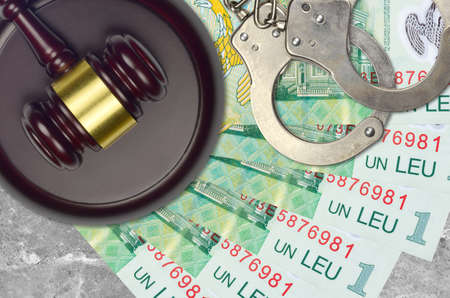 1 Romanian leu bills and judge hammer with police handcuffs on court desk. Concept of judicial trial or bribery. Tax avoidance or tax evasion