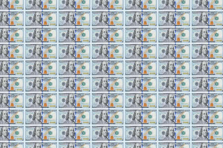 100 US dollars bills printed in money production conveyor. Collage of many bills. Concept of currency inflation and devaluation