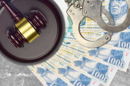 1000 Hungarian forint bills and judge hammer with police handcuffs on court desk. Concept of judicial trial or bribery. Tax avoidance or tax evasion