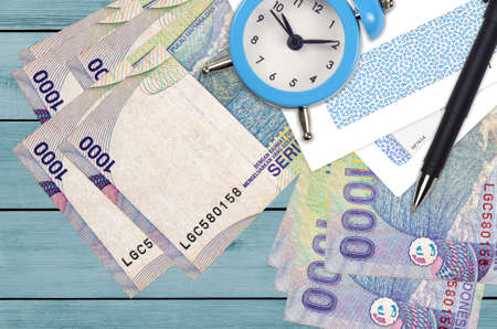 1000 Indonesian rupiah bills and alarm clock with pen and envelopes. Tax season concept, payment deadline for credit or loan. Financial operations using postal service. Quick money transfer