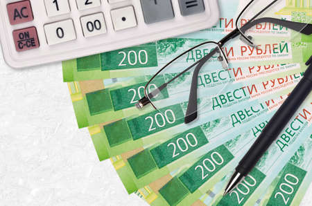 200 russian rubles bills fan and calculator with glasses and pen. Business loan or tax payment season concept. Financial planning