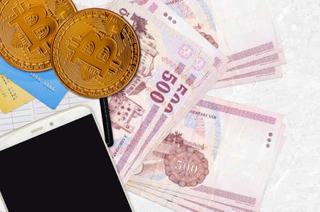 500 Hungarian forint bills and golden bitcoins with smartphone and credit cards. Cryptocurrency investment concept. Crypto mining or trading transactions