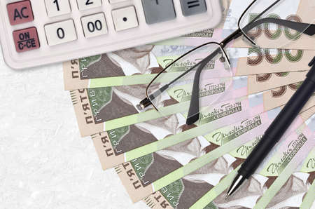 500 Ukrainian hryvnias bills fan and calculator with glasses and pen. Business loan or tax payment season concept. Financial planning Standard-Bild