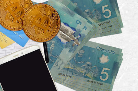 5 Canadian dollars bills and golden bitcoins with smartphone and credit cards. Cryptocurrency investment concept. Crypto mining or trading transactions