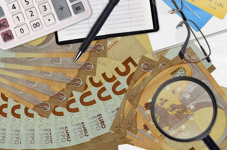 50 euro bills and calculator with glasses and pen. Tax payment season concept or investment solutions. Searching a job with high salary earnings