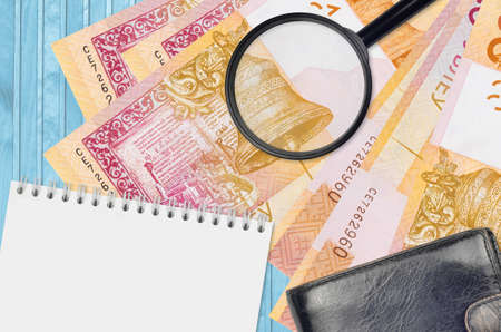 20 Belorussian rubles bills and magnifying glass with black purse and notepad. Concept of counterfeit money. Search for differences in details on money bills to detect fake money