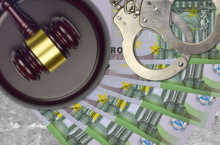 100 Euro bills and judge hammer with police handcuffs on court desk. Concept of judicial trial or bribery. Tax avoidance or tax evasion