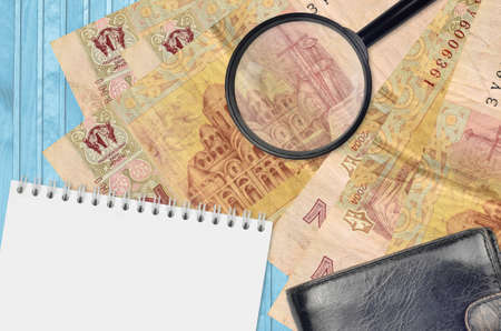 2 Ukrainian hryvnias bills and magnifying glass with black purse and notepad. Concept of counterfeit money. Search for differences in details on money bills to detect fake money
