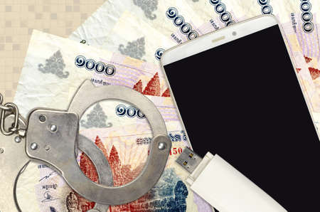 1000 Cambodian riels bills and smartphone with police handcuffs. Concept of hackers phishing attacks, illegal scam or online spyware soft distribution Stok Fotoğraf