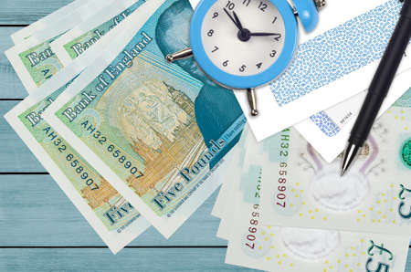 5 British pounds bills and alarm clock with pen and envelopes. Tax season concept, payment deadline for credit or loan. Financial operations using postal service. Quick money transfer