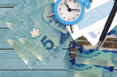 5 Canadian dollars bills and alarm clock with pen and envelopes. Tax season concept, payment deadline for credit or loan. Financial operations using postal service. Quick money transfer