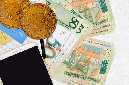 50 Belorussian rubles bills and golden bitcoins with smartphone and credit cards. Cryptocurrency investment concept. Crypto mining or trading transactions