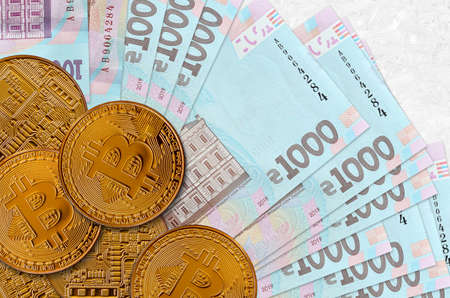 1000 Ukrainian hryvnias bills and golden bitcoins. Cryptocurrency investment concept. Crypto mining or trading transactions