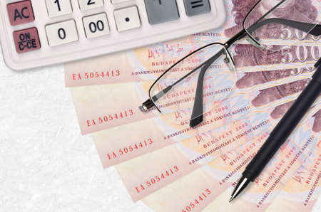 500 Hungarian forint bills fan and calculator with glasses and pen. Business loan or tax payment season concept. Financial planning