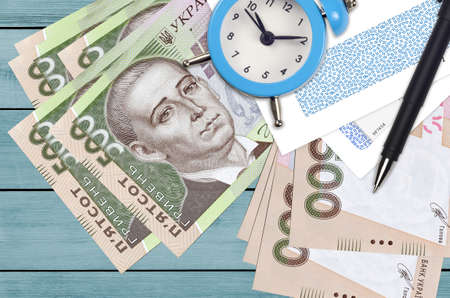 500 Ukrainian hryvnias bills and alarm clock with pen and envelopes. Tax season concept, payment deadline for credit or loan. Financial operations using postal service. Quick money transfer