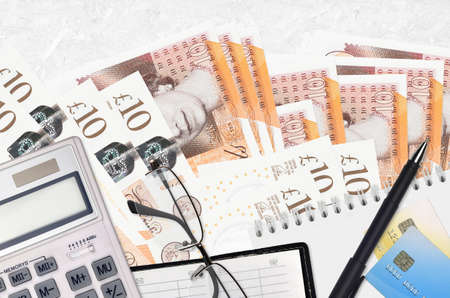 10 British pounds bills and calculator with glasses and pen. Tax payment season concept or investment solutions. Financial planning or accountant paperwork