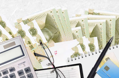 1 Chinese yuan bills and calculator with glasses and pen. Tax payment season concept or investment solutions. Financial planning or accountant paperwork