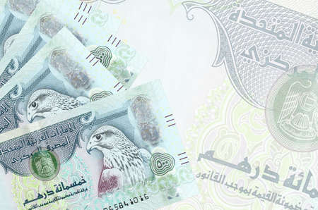 500 UAE dirhams bills lies in stack on background of big semi-transparent banknote. Abstract business background with copy space