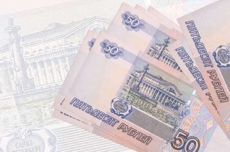 50 russian rubles bills lies in stack on background of big semi-transparent banknote. Abstract presentation of national currency. Business concept