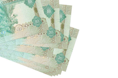 10 UAE dirhams bills lies in small bunch or pack isolated on white. Mockup with copy space. Business and currency exchange concept