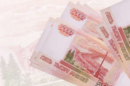 5000 russian rubles bills lies in stack on background of big semi-transparent banknote. Abstract presentation of national currency. Business concept