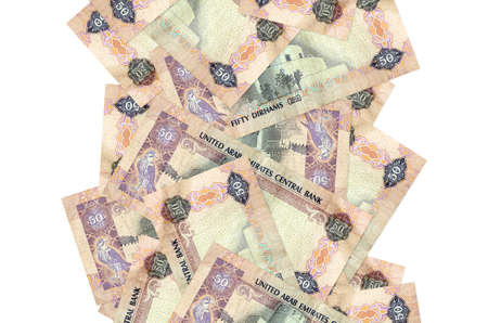 50 UAE dirhams bills flying down isolated on white. Many banknotes falling with white copy space on left and right side