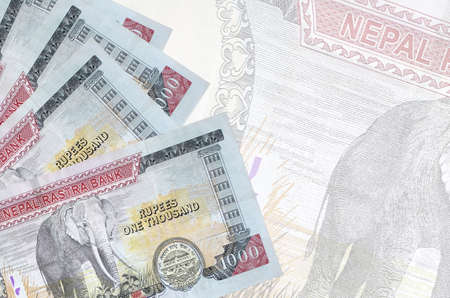 1000 Nepalese rupees bills lies in stack on background of big semi-transparent banknote. Abstract business background with copy space