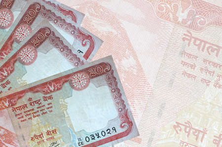 20 Nepalese rupees bills lies in stack on background of big semi-transparent banknote. Abstract business background with copy space