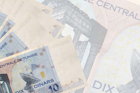 10 Tunisian dinars bills lies in stack on background of big semi-transparent banknote. Abstract business background with copy space Stock fotó