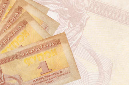 1 Ukrainian coupon bills lies in stack on background of big semi-transparent banknote. Abstract business background with copy space