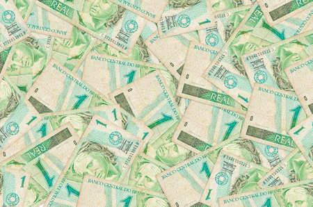 1 Brazilian real bills lies in big pile. Rich life conceptual background. Big amount of money
