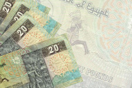 20 Egyptian pounds bills lies in stack on background of big semi-transparent banknote. Abstract business background with copy space