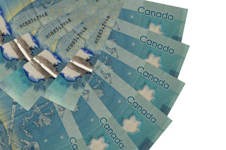 5 Canadian dollars bills lies isolated on white background with copy space stacked in fan shape close up. Financial transactions concept 스톡 콘텐츠
