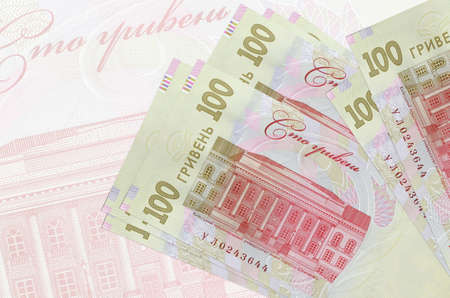 100 Ukrainian hryvnias bills lies in stack on background of big semi-transparent banknote. Abstract presentation of national currency. Business concept