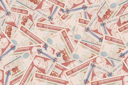 100 Guatemalan quetzales bills lies in big pile. Rich life conceptual background. Big amount of money 스톡 콘텐츠