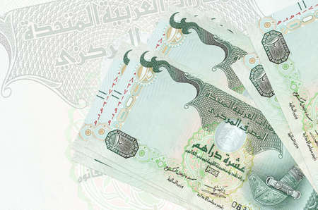 10 UAE dirhams bills lies in stack on background of big semi-transparent banknote. Abstract presentation of national currency. Business concept Banco de Imagens