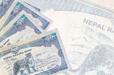 50 Nepalese rupees bills lies in stack on background of big semi-transparent banknote. Abstract business background with copy space