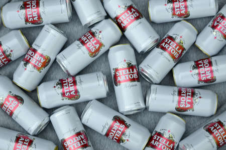 KHARKOV, UKRAINE - AUGUST 22 2020: Many tin cans of Stella Artois beer outdoors. Stella Artois is the most famous Belgian beer in the world owned by AB InBev