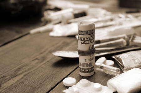Roll of hundred dollar bills on background of narcotic drug dealer stuff. Concept of heavy drug addiction and amphetamine trafficking in USA