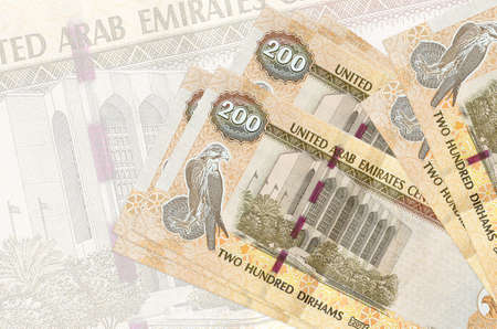 200 UAE dirhams bills lies in stack on background of big semi-transparent banknote. Abstract presentation of national currency. Business concept Banco de Imagens