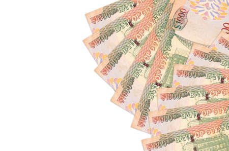 1000 Guyanese dollars bills lies isolated on white background with copy space. Rich life conceptual background. Big amount of national currency wealth