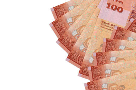 100 Sri Lankan rupees bills lies isolated on white background with copy space. Rich life conceptual background. Big amount of national currency wealth