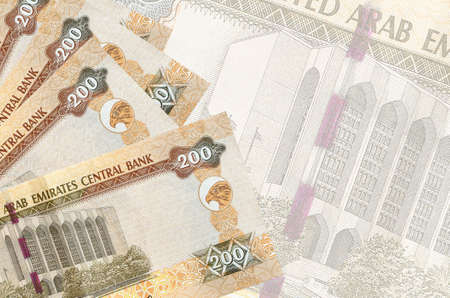 200 UAE dirhams bills lies in stack on background of big semi-transparent banknote. Abstract business background with copy space