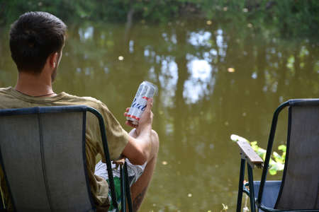 KHARKOV, UKRAINE - AUGUST 22 2020: Man holds Budweiser Lager Alcohol Beer during fishing. Budweiser is Brand from Anheuser-Busch Inbev most popular in America
