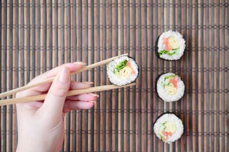 A hand with chopsticks holds a sushi roll on a bamboo straw serwing mat background. Traditional Asian food. 免版税图像