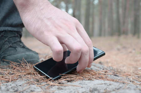 Male hand picking up a lost mobile phone from a ground in autumn fir wood path. The concept of finding a valuable thing and good luck 免版税图像