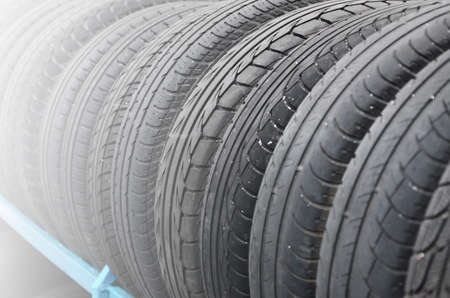 Rack with variety of car tires in automobile store. Many black tires. Tire stack background. Selective focus 免版税图像